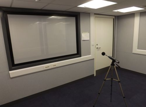 A photo of an audiology room with fabric covered acoustic walls, door and vision panel
