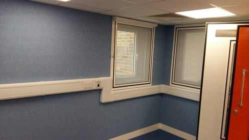 A photo of an audiology room with fabric covered acoustic walls, acoustic windows and an acoustic door