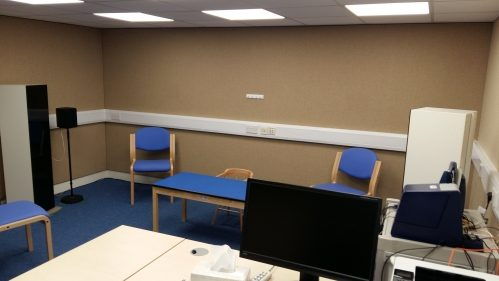 A photo of an audiology room with fabric covered acoustic walls