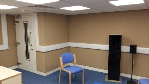 A photo of an audiology room with fabric covered acoustic walls and an acoustic door